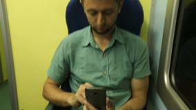 Man sitting by window on train at night and typing message on his mobile phone. Stock footage stock video footage