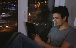 Man is sitting on the windowsill in the dark night and browsing web on tablet. Man is sitting on the windowsill in the dark night and browsing web on tablet Stock Photo