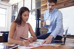 Man sitting on a woman`s desk discusses work with her Stock Photography