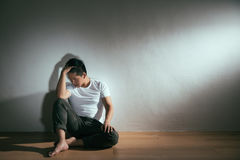 Man sitting on wood floor alone relaxing. Worried about thinking horrible things become crazy calming resting in white wall background at dark studio room Stock Photo