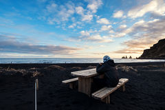 A man sitting on wooden bench at Black Sand Beach in sunset. A man relaxing on wooden bench at Black Sand Beach in sunset Stock Photos