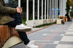 Man sitting on a wooden bench in the street Royalty Free Stock Images
