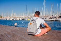 Man on dock, Barcelona, Spain. Man sitting on wooden dock next to seagull wearing backpack in harbor of Barcelona, Spain on sunny day royalty free stock photos