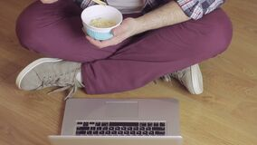 A man sitting on a wooden floor typing text on the laptop keyboard and eating noodles with chopsticks. A man sitting cross-legged on a wooden floor typing text stock footage