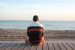 Man Sitting on Wooden Panel Facing in the Ocean Royalty Free Stock Images