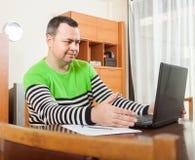 Man sitting at work on laptop. Man sitting at computer in home interior royalty free stock image