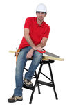 Man sitting on a workbench. Man with a saw sitting on a workbench Stock Image
