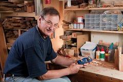 Man sitting at workbench in workshop. Senior man sitting at workbench in workshop with plane Stock Photo