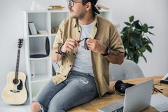 Man sitting on worktable. Young handsome man sitting on worktable and looking away Royalty Free Stock Photo