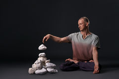 Man sitting in yoga pose with white stones near by Stock Photo
