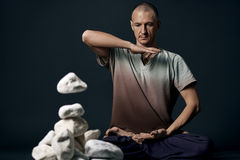 Man sitting in yoga pose with white stones near by Royalty Free Stock Photo