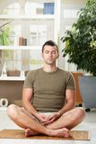 Man sitting in yoga position Royalty Free Stock Image