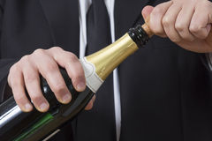 Man in siut opening Champagne bottle Royalty Free Stock Photos