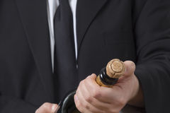 Man in siut opening Champagne bottle Royalty Free Stock Photo