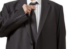 Man in siut straightening his tie Stock Photos