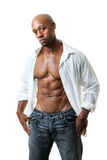 Man with Six Pack Abs. Toned and ripped lean muscle fitness man wearing an open shirt and jeans isolated over a white background Royalty Free Stock Photos