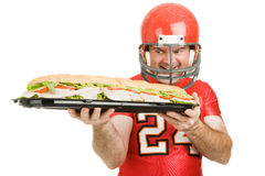 Man Sized Hunger. Football player hungrily looking at a giant submarine sandwich. Isolated on white stock photography