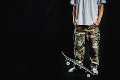 Man with skateboard on a black background Stock Photography