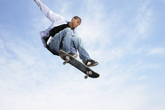 Man On Skateboard In Midair. Low angle view of young man on skateboard in midair against cloudy sky royalty free stock photography