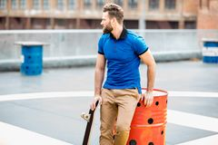 Man with skateboard outdoors stock photo