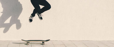 Man And Skateboard. Young man in red shirt jumping on skateboard Stock Image