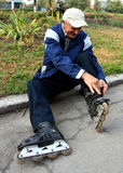 Man and skates. An elderly man wears roller skates Royalty Free Stock Photos