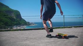 A man skating on a penny board on an observation deck and looking at the sea. Mid shot stock footage