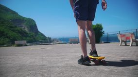 A man skating on a penny board on an observation deck. Mid shot stock footage