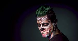 Man with skeleton face makeup and evil smile. Mystical skull makeup for Halloween stock video footage