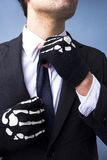 Man with skeleton gloves adjusting his tie. Young man with skeleton gloves adjusting his tie Royalty Free Stock Photo