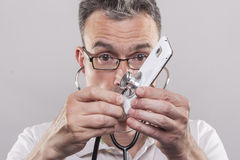 Man with skeptical look holding a stethoscope to a smartphone Royalty Free Stock Photography