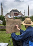 A man sketches the magnificent Aya Sofya in the Sultanahmet district of Istanbul in Turkey. Stock Photos