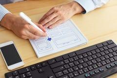 Man sketching design on paper. Man sketching on paper webdesign behind the desk Royalty Free Stock Photo