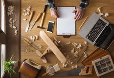 Man sketching a DIY project at home. On a clipboard with tools and wood shavings all around, top view Stock Photography