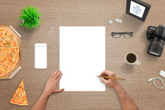 Man sketching on empty white paper. Top view of desk. White smart phone with blank screen for mockup. Digital camera, pizza, plant, glasses, coffee, photo stock photo