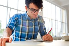 Man sketching. Modern student with pencil sketching in copybook by desk Stock Photo