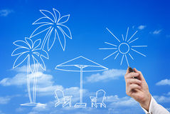 Man sketching a tropical beach scene. Hand of a man sketching a tropical beach scene in the blue sky with palm trees, comfortable chairs, sunshine and a beach Stock Images