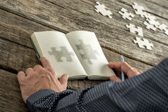 Man sketching two matchng puzzle pieces in his notepad Stock Photography