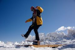 Man in ski equipment and safety glasses balances on a snowboard. Man in ski equipment, helmet and safety glasses balances on a snowboard in the snow against a Stock Photos