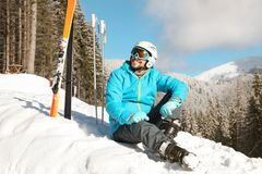 Man with ski equipment sitting on snow in mountains royalty free stock photography