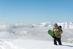 Man wearing goggles and a green snowboard in his hands wanders knee-deep in the snow. Man in ski equipment, wearing goggles and a green snowboard in his hands Stock Photography
