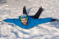 Man with ski goggles is having fun at winter. Smiling man is lyi. Ng on the snow. Snowboarder  wearing winter jacket.  Snowy winter.Smiling man is lying on the Stock Photography