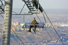 Man on the ski lift. Above city landscape Stock Photo