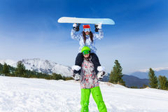 Man in ski mask holding girl with board up head Royalty Free Stock Image