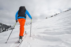 Man with ski mountaineering climb towards the summit. Man alone with ski mountaineering climb towards the summit Royalty Free Stock Photo