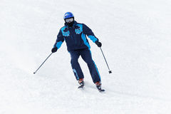 Man in ski suit glides downhill on skis Stock Photography