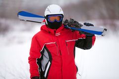 Man in a ski suit with skis Stock Photography