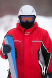 Man in a ski suit with skis Royalty Free Stock Images