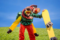 Man in ski suits giving piggyback ride to girlfriend with snowbo Stock Photos