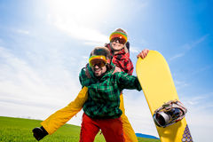 Man in ski suits giving piggyback ride to girlfriend with snowbo Royalty Free Stock Photo